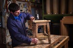 恢复板凳家具的木匠在他的车间 免版税库存照片