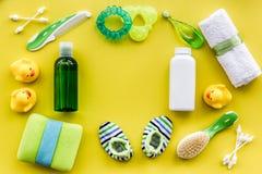 巴恩化妆用品为文本的孩子、毛巾和玩具黄色背景顶视图空间设置了 免版税库存照片