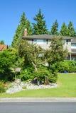 恰好环境美化的前院有装饰画得好的住宅房子 免版税库存照片