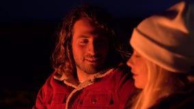 恰好聊天年轻的夫妇特写镜头射击坐由火和 野营与由海的帐篷 r 股票视频