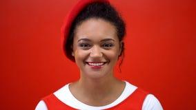 恳切地微笑在红色背景,秀丽的照相机的快乐的年轻女人 免版税库存照片