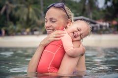恳切地拥抱他的母亲的婴孩在海滩假日期间 象征婴孩关心和爱的概念性图片 免版税库存图片