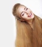 恳切的微笑。有流动的健康头发的欢腾的少妇。乐趣 免版税库存图片