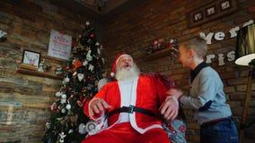 恶作剧男孩意想不到的出现在圣诞老人前面的在有高圣诞树的美妙地装饰的室 股票视频