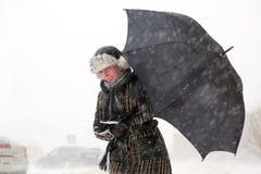有伞的女孩在雪风暴期间 库存图片