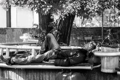 恶劣的饥饿和疲乏的无家可归的经验丰富的人前军事战士睡眠在长凳的树荫下在都市城市街道社会documen 免版税库存照片