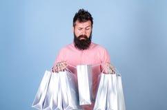 恶心面孔购物的shopaholic的行家使上瘾或 在销售季节的人购物与折扣 刮胡须人 库存照片
