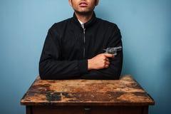 恶棍在与枪的桌上 免版税库存照片