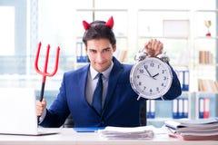 恶魔恼怒的商人在办公室 免版税库存照片
