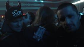 恶魔的朋友打扮摆在照相机的在人群万圣夜夜总会党 影视素材