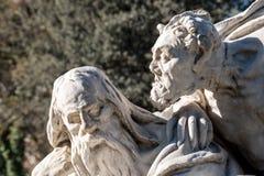 恶魔的雕象谈话与一个人 免版税库存图片