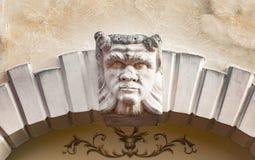 恶魔头在意大利别墅的石曲拱上雕刻了 免版税图库摄影