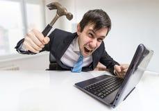 恼怒和疯狂的人与膝上型计算机一起使用 他损坏有锤子的笔记本 免版税库存图片