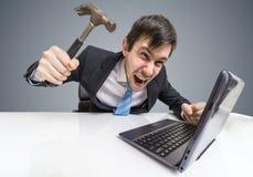 恼怒和疯狂的人与膝上型计算机一起使用 他损坏有锤子的笔记本 免版税库存照片