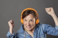 恼怒的中部变老了妇女皱眉的听到噪声或音乐 免版税库存图片