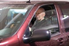 恼怒的中部驾驶汽车的年迈的人 免版税库存图片