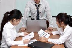 恼怒的亚裔上司人抱怨的雇员在会议期间在会议室 库存图片