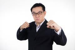恼怒的亚裔中国人佩带的衣服和握两拳头 免版税库存照片