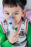 恼怒的亚裔孩子特写镜头拿着trea的一台面具蒸气吸入器 库存图片