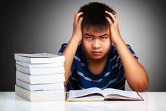 恼怒的亚裔男孩有学习困难 库存照片