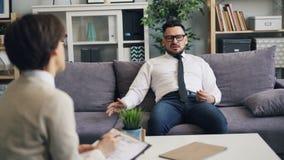 恼怒的人商人谈话与关于愤怒管理的心理学家在办公室 股票录像
