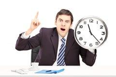 恼怒的人在办公室,举行时钟和指向 免版税库存照片