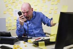 恼怒的人尖叫在电话 库存图片