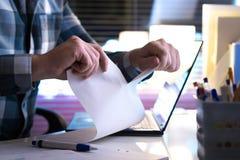 恼怒的人撕毁的纸在半家或在现代办公室 免版税库存照片