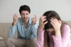 恼怒的人疯狂对女朋友,呼喊在她,夫妇争吵 免版税库存图片