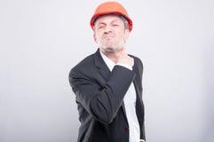 恼怒的做切口脖子姿态的承包商佩带的安全帽 免版税图库摄影