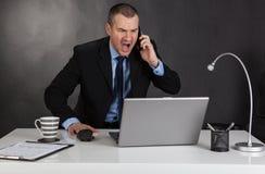 恼怒的商人在办公室 库存图片