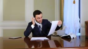 恼怒的商人有与某人的一次激昂的交谈输送路线电话的 库存照片