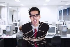 恼怒的商人栓与绳索在办公室 库存图片