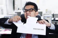 恼怒的商人泪花纸在办公室 免版税库存图片