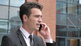 恼怒的商人谈话在电话,当走与办公室时 股票视频