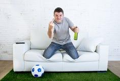 恼怒的在打手势翻倒的电视在家长沙发的橄榄球狂热爱好者观看的比赛 免版税库存照片