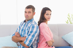 恼怒的在沙发横渡的夫妇坐的胳膊 免版税库存图片
