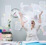 恼怒的在空气的女实业家投掷的文书工作 库存照片