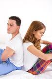 恼怒的夫妇彼此的挡回在床上 免版税库存照片
