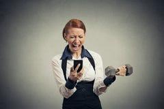 恼怒的女商人尖叫在手机举的哑铃 免版税库存图片