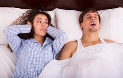 恼怒的女孩疲倦于大声的男朋友打鼾 免版税图库摄影