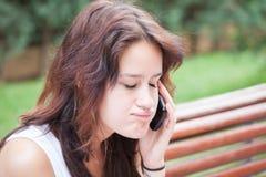 恼怒的女孩谈话在有闭合的眼睛的手机 免版税库存照片