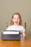 恼怒的女孩,当工作在老打字机时 免版税图库摄影
