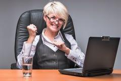 恼怒的女实业家与膝上型计算机一起使用在办公室 免版税库存图片