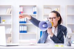 恼怒的女实业家叫喊与扩音器在办公室 免版税库存图片