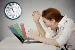 恼怒的女实业家尖叫对计算机,迫使由缺乏时间 免版税库存照片