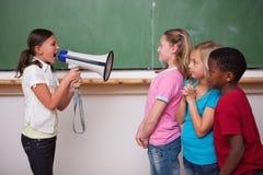 恼怒的女小学生尖叫通过扩音机 库存图片