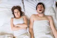 恼怒的妇女伪善言辞睡眠和听打鼾她的丈夫 免版税库存图片