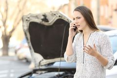 恼怒的妇女叫保险在汽车故障以后 库存图片