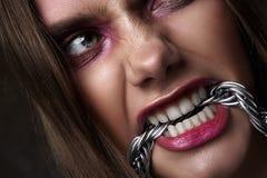 恼怒的妇女叮咬链子 传神秀丽神色 库存照片